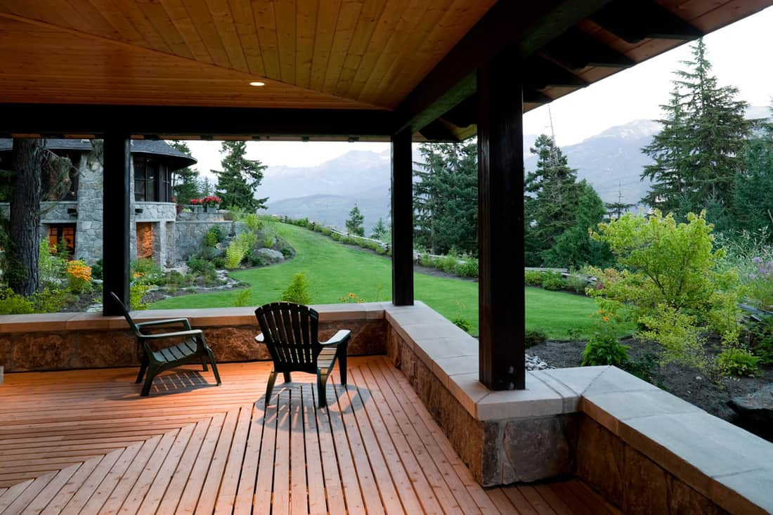 Open balcony with wooden decking and wooden black chairs