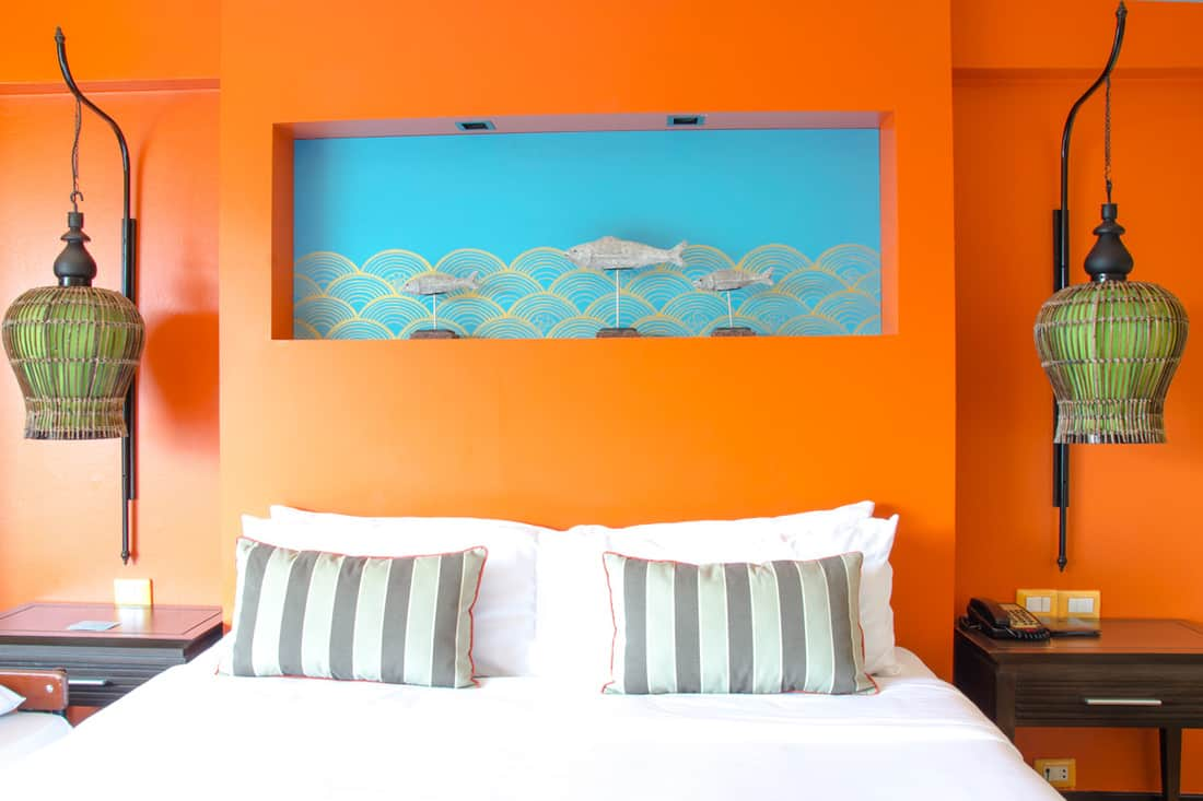 Orange colored wall with cool hanging lamps and a white bedding set with stripped pillows