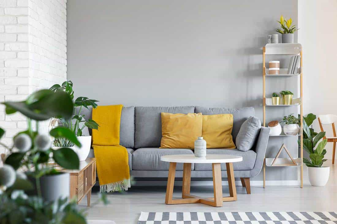 Orange pillows and blanket on grey couch in living room interior with wooden table
