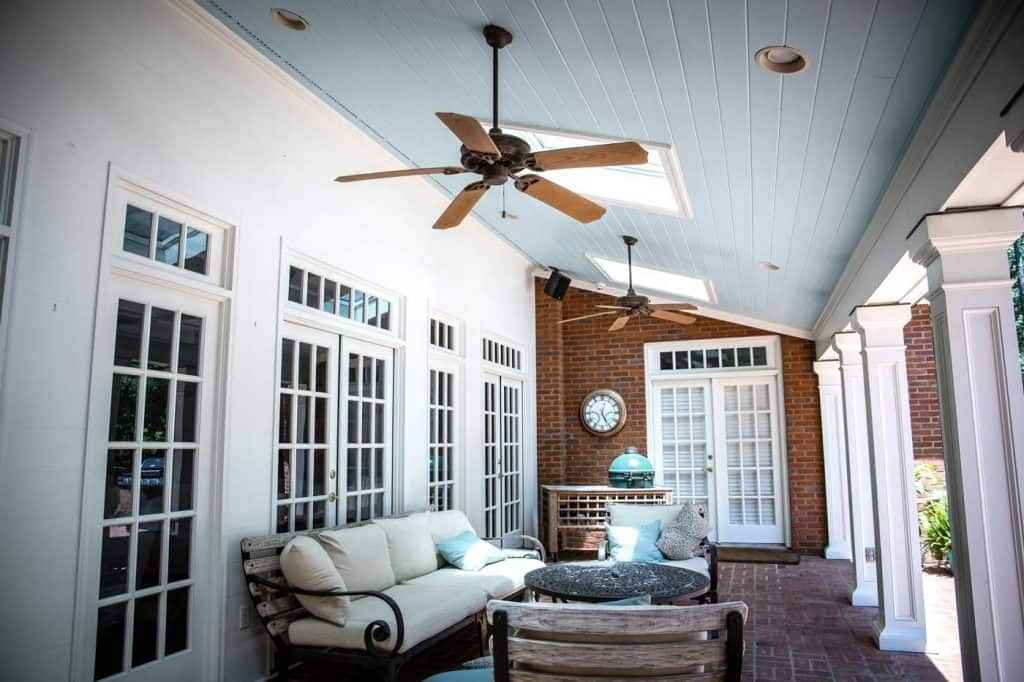 Outdoor front porch patio with outdoor seating and a large fan and table