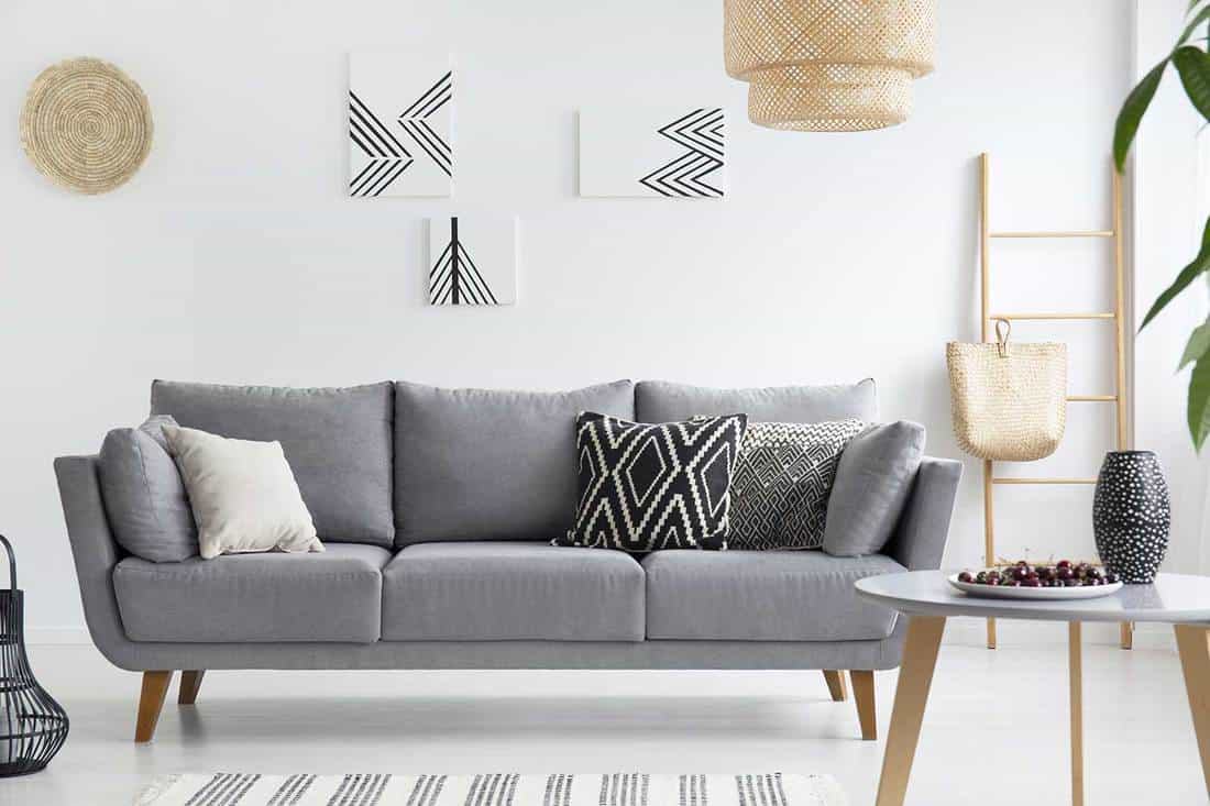 Pillows on grey sofa in white living room interior with posters, lamp and wooden table