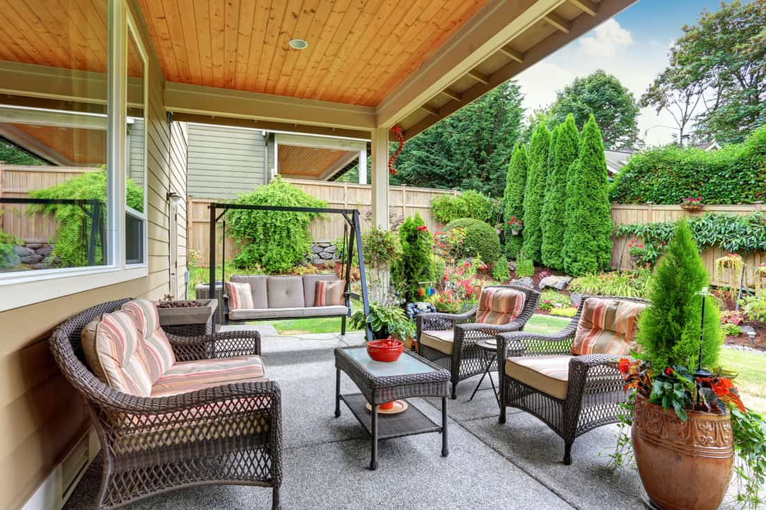 Porch with rattan chairs with gorgeous garden in front