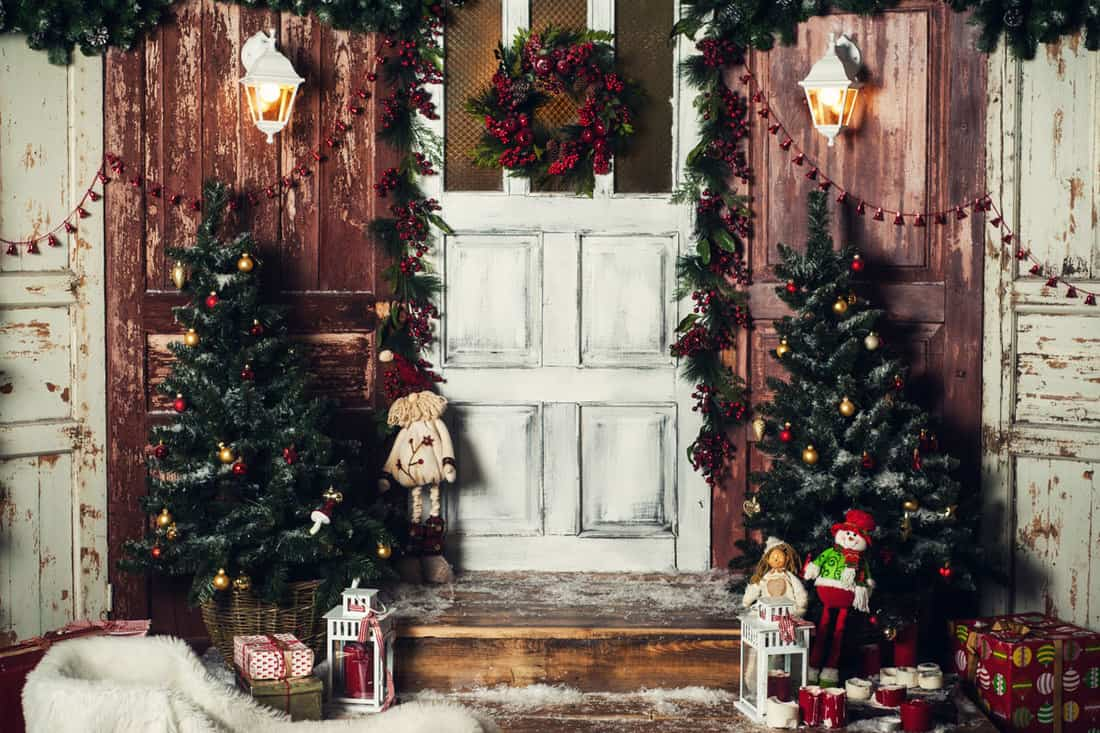 Porch with small Christmas tree on the door step decorated with Christmas balls