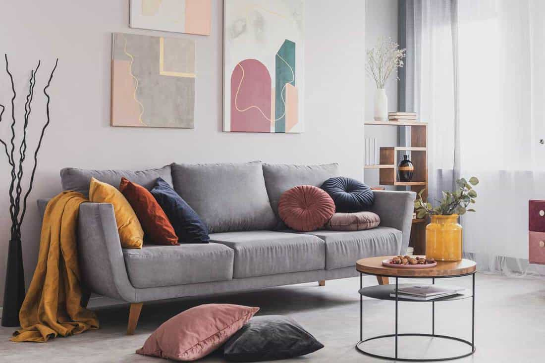 Real photo of abstract paintings hanging on white wall above a gray sofa with cushion in a living room interior with big windows, How Much Does it Cost to Replace Sofa Cushions?
