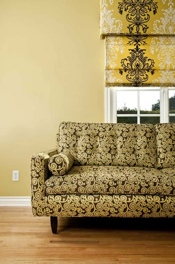 Retro couch with patterned fabric in empty domestic room with wood flooring and yellow walls