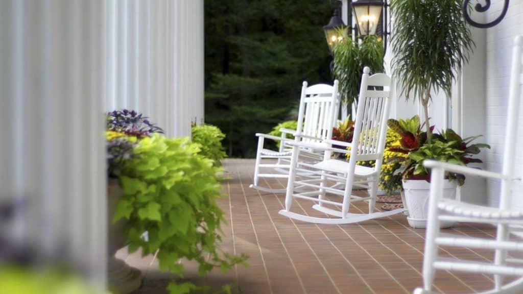 Krzesła bujane siedzące na zewnątrz na frontowej werandzie domu z białymi kolumnami.