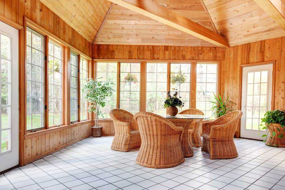 Rustic living room with wooden walls, wooden ceiling, and wooden chairs