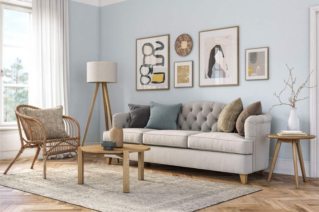 Small light blue colored wall living room with gray couch with pictures above it