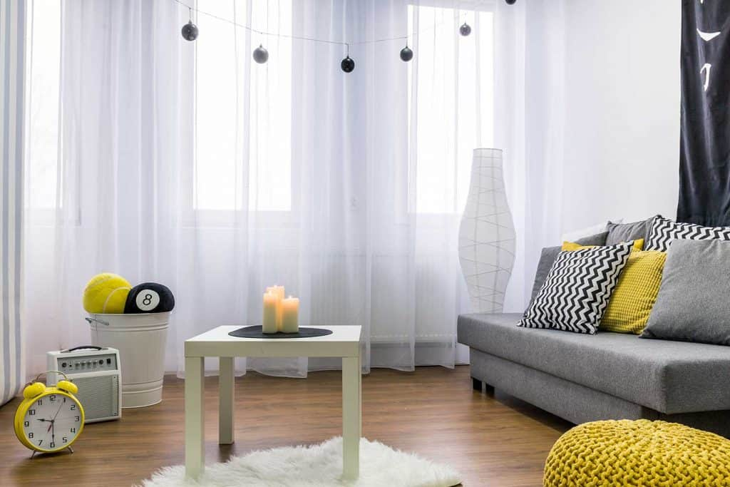 Small living room interior with cozy couch and candles on the coffee table