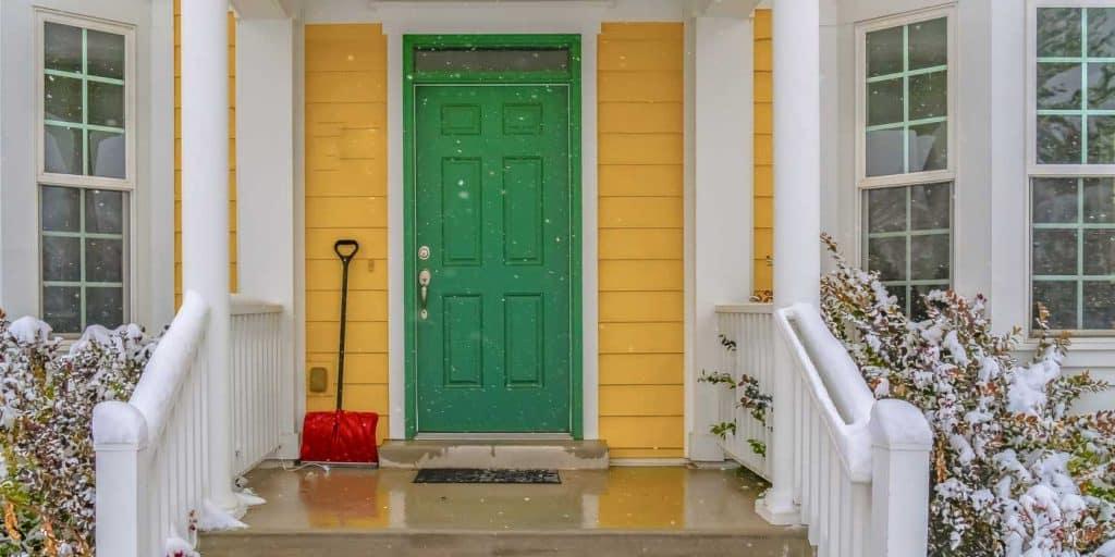 Snow showel beside the green front door of a home.
