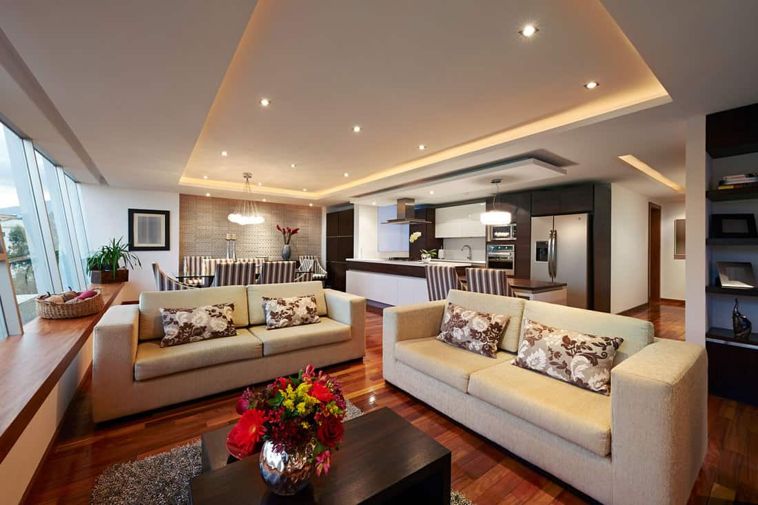 Spacious living room with brown colored sofas and a gorgeous wood tile flooring