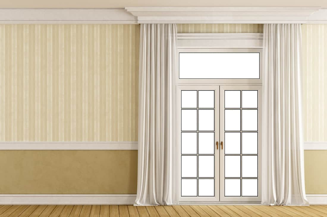 Striped beige colored walls with double door and white curtains on the sides