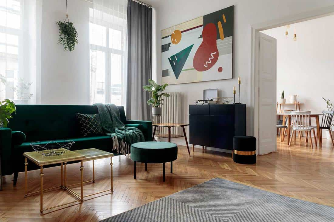 Stylish living room with green velvet sofa and abstract art on wall