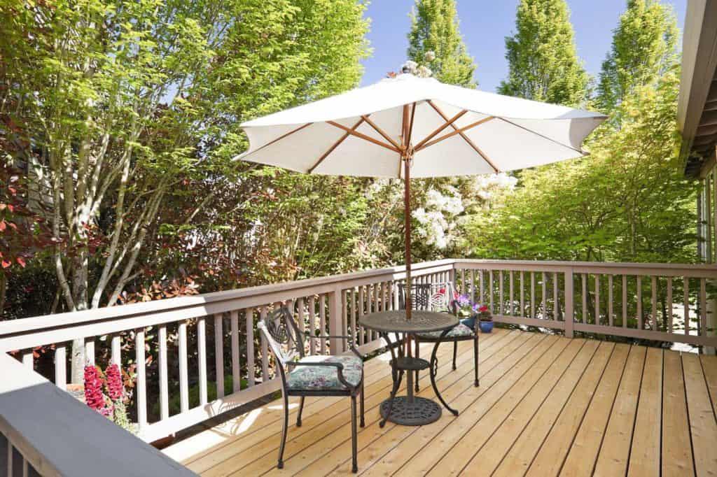 Słoneczny ganek ze stołem, krzesłami i parasolem.