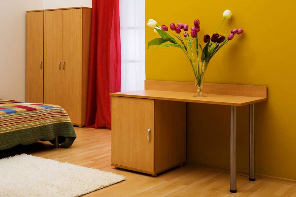 Table with a bouquet of tulips on a yellow wall bedroom