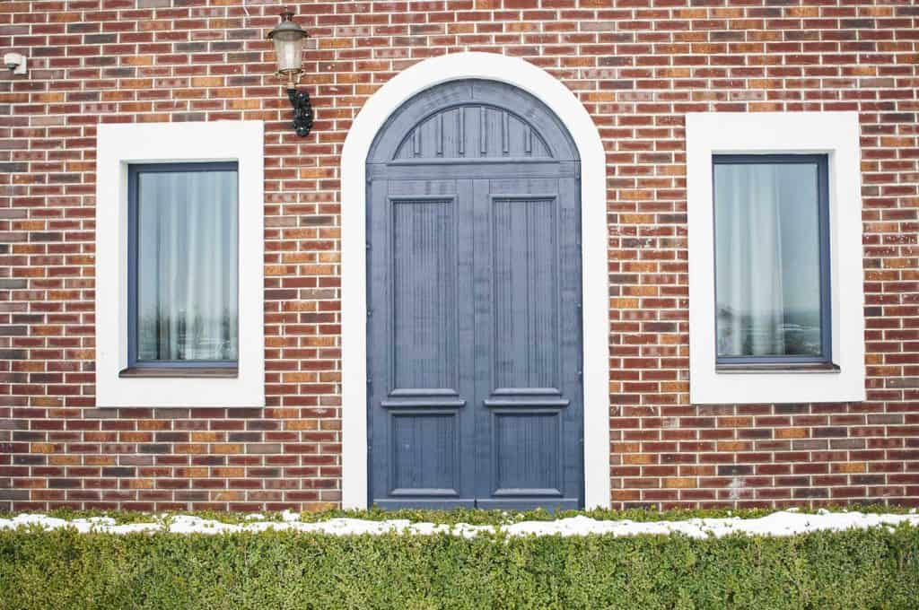 The facade of the house with a blue arched door