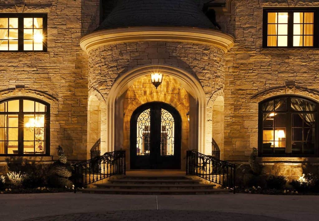 The front door of a large mansion with a circular driveway at night
