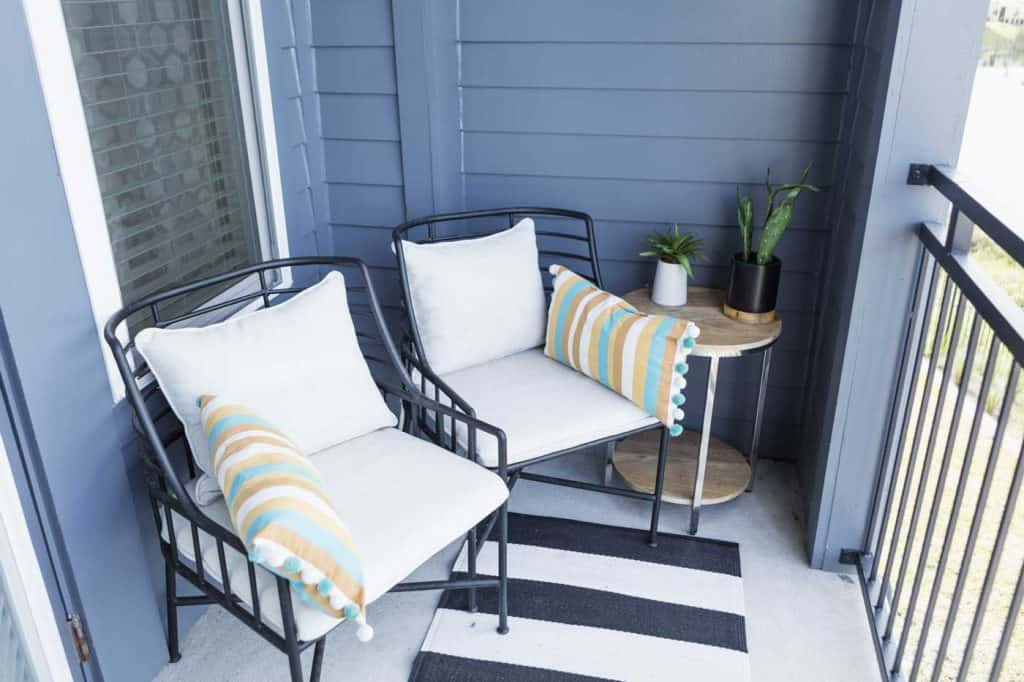Two empty chairs on a cozy front porch or balcony. A small side table with houseplants is next to one of the chairs.