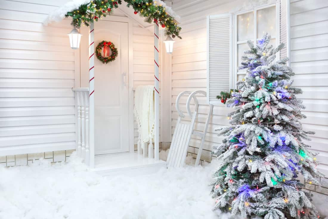 White colored house with Christmas tree outside and wreath at the door