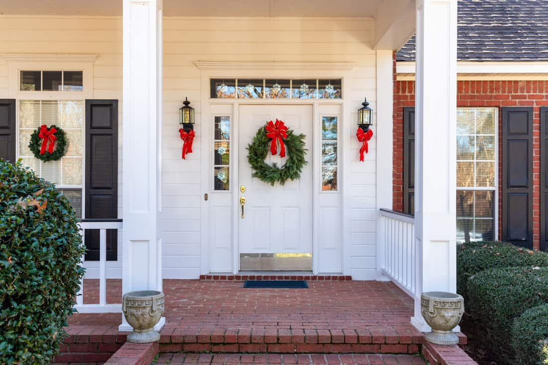 White colored porch with wreath at the door and red ribbons on the wall lamps on both sides
