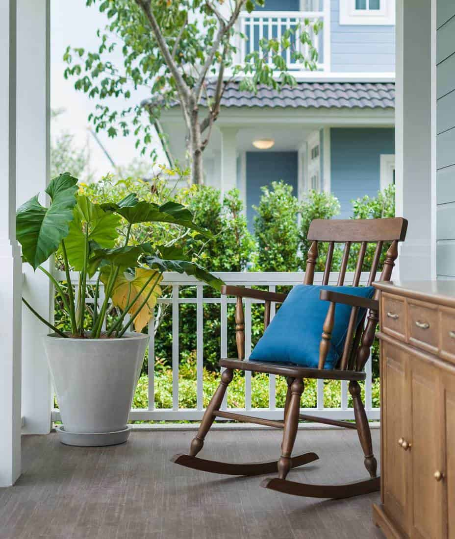 Wooden rocking chair on front porch with pillow