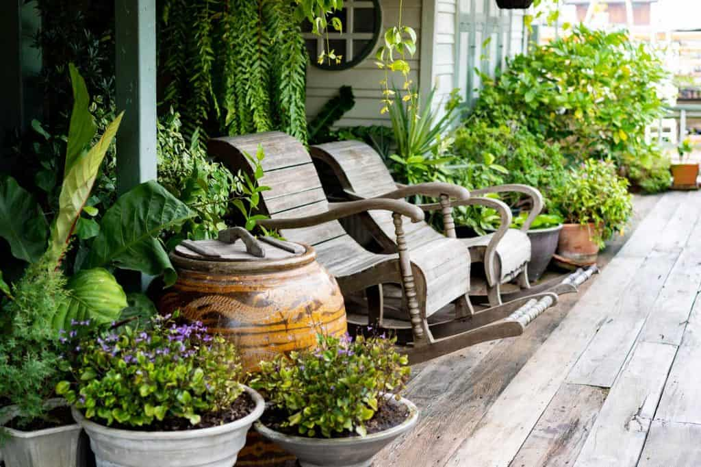 Wooden rocking chairs in a cottage front porch setting on wooden floor in vintage Thai botanical garden, with traditional Thai old water jar decoration.