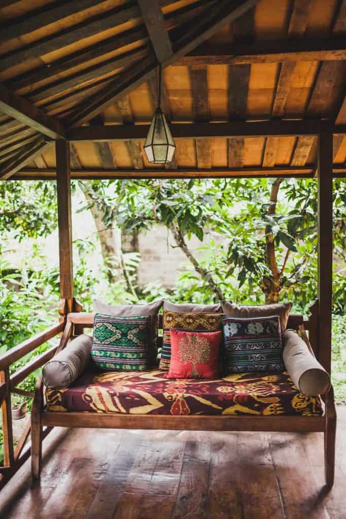 Wooden sofa with pillows on the front porch under roof in ethnic style with colorful traditional ornaments