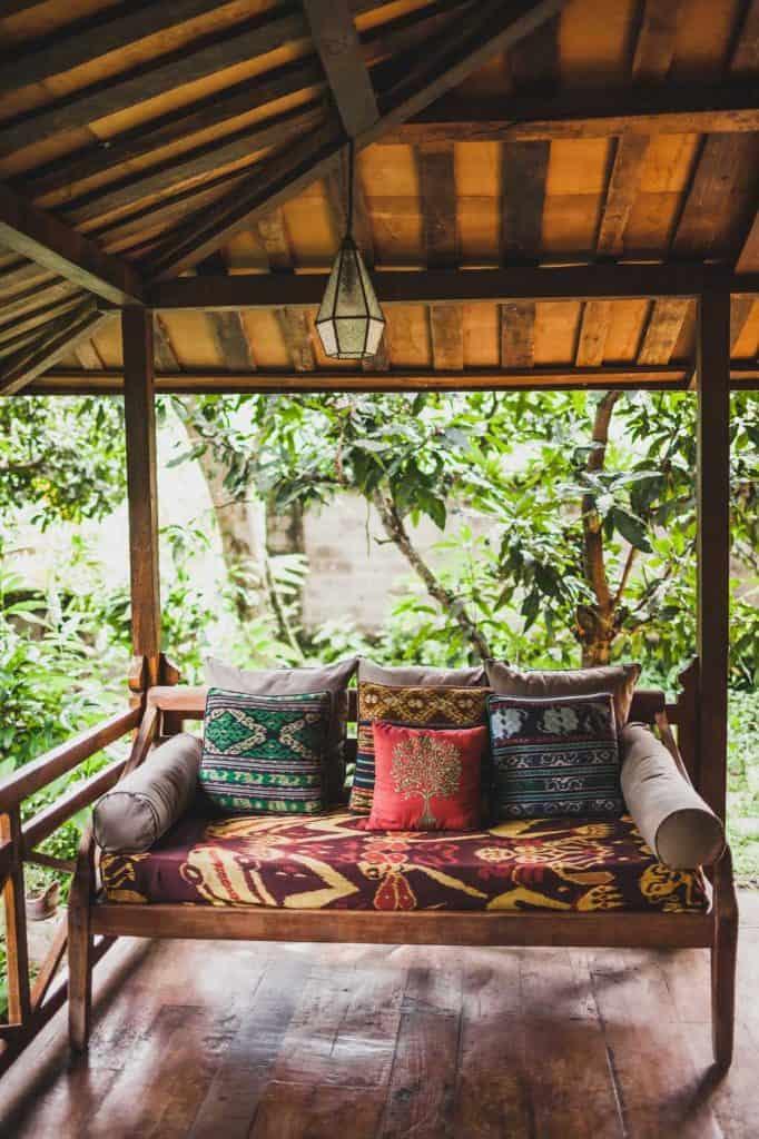 Drewniana kanapa z poduszkami na werandzie pod dachem w stylu etnicznym z kolorowymi tradycyjnymi ornamentami