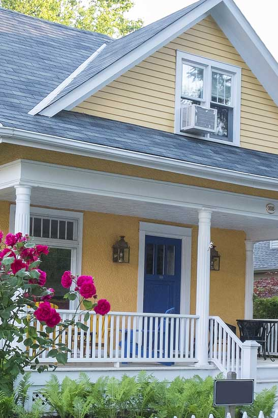 Yellow House with a blue door Pink Rose Bush in Front