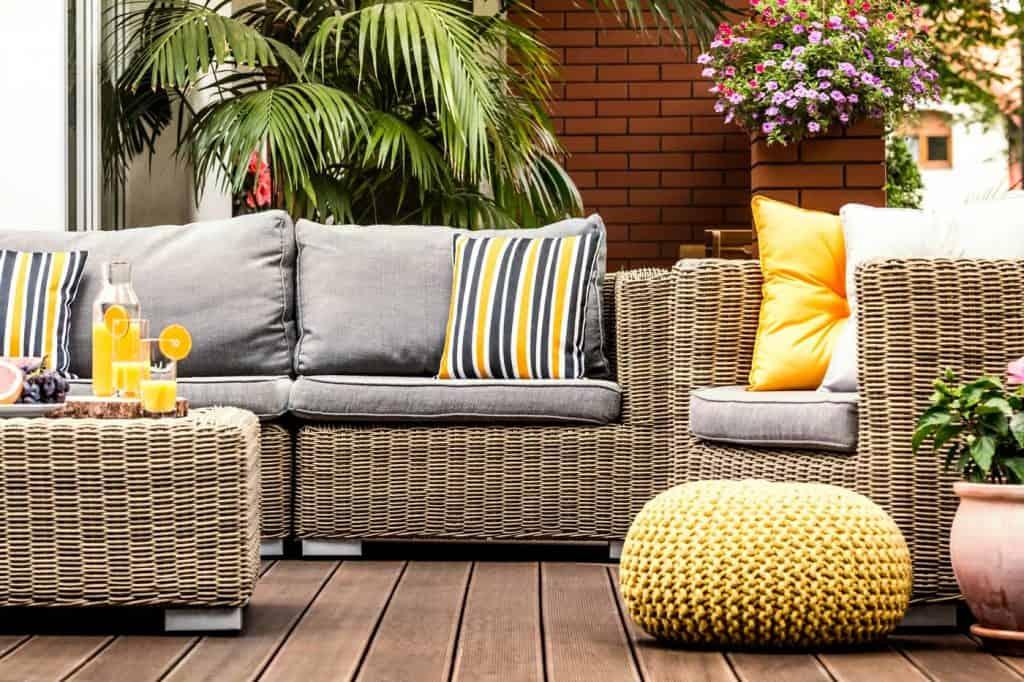 Żółta pufa obok fotela rattanowego na drewnianej werandzie z pasiastymi poduszkami na sofie
