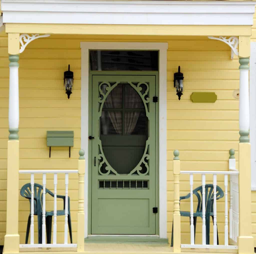 a meticulously painted yellow victorian home with an ornate spring green door