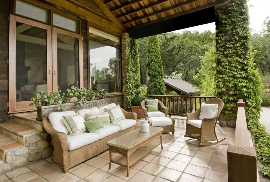 dom z ładnym gankiem, drewniane podwójne drzwi, meble z wikliny, meksykańskie płytki, podłoga z kostki brukowej