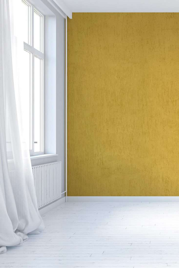 Empty antique interior with mustard yellow textured plaster wall and hardwood floor