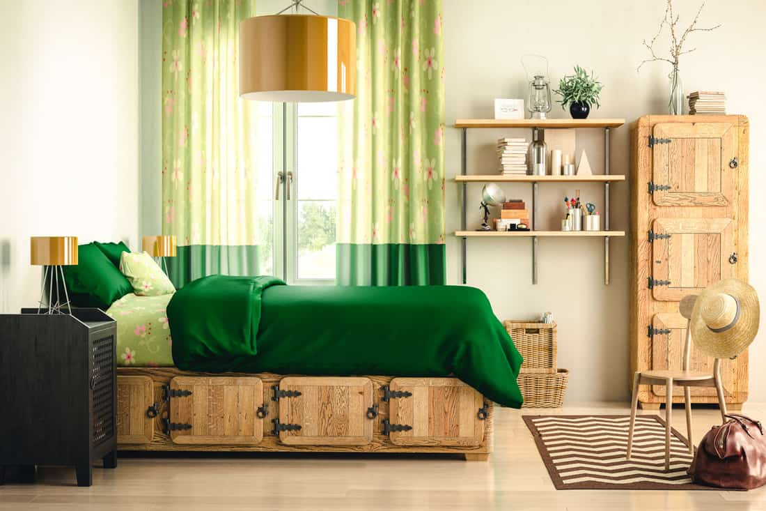 A bedroom with a green bed and green colored curtains