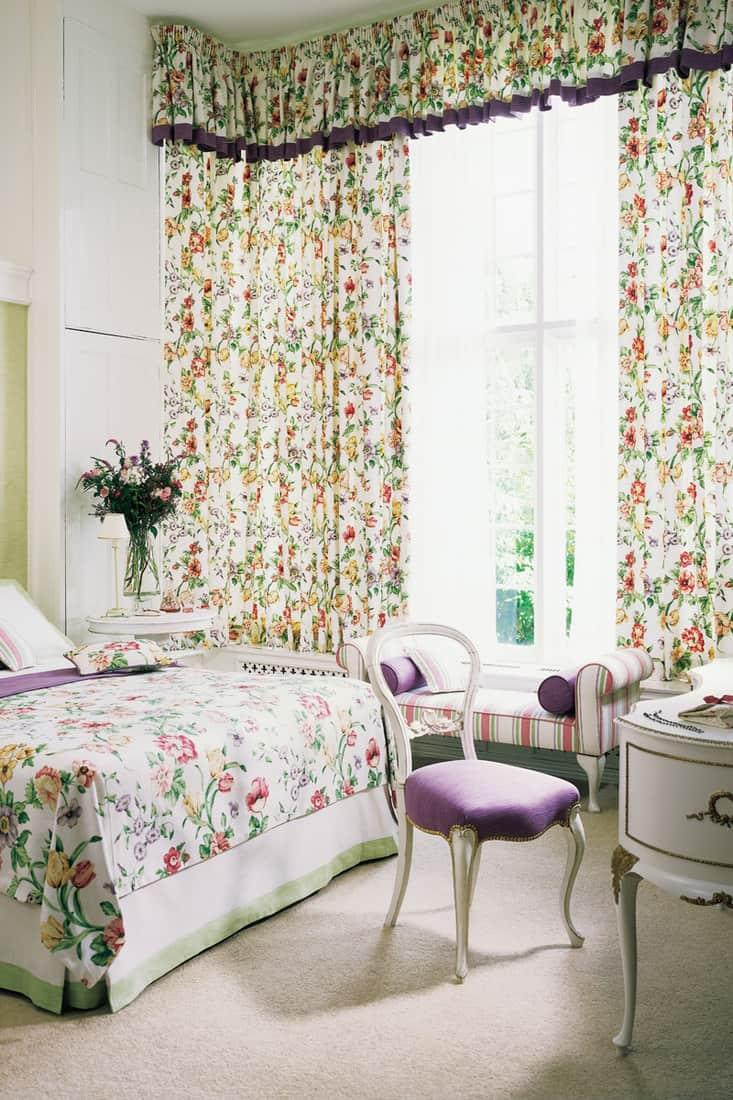 A bedroom with floral patterned curtains and a floral bedding set