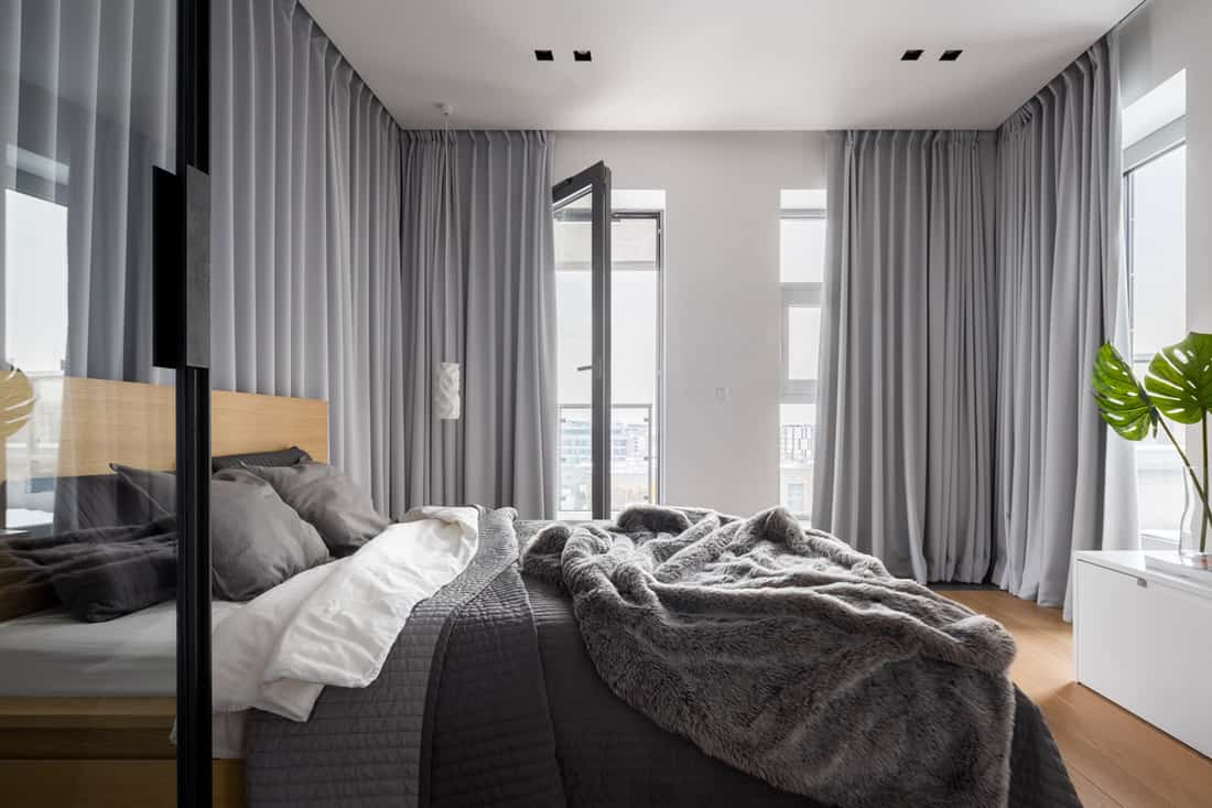 A bedroom with gray colored curtains, gray bedding set, and white colored walls