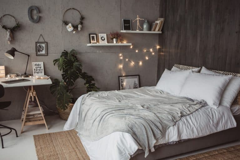 A bedroom with white bedding sets, small Christmas light on the side and a wallpaper pattern on the background, 13 Bedroom Decor Gift Ideas that You'll Love