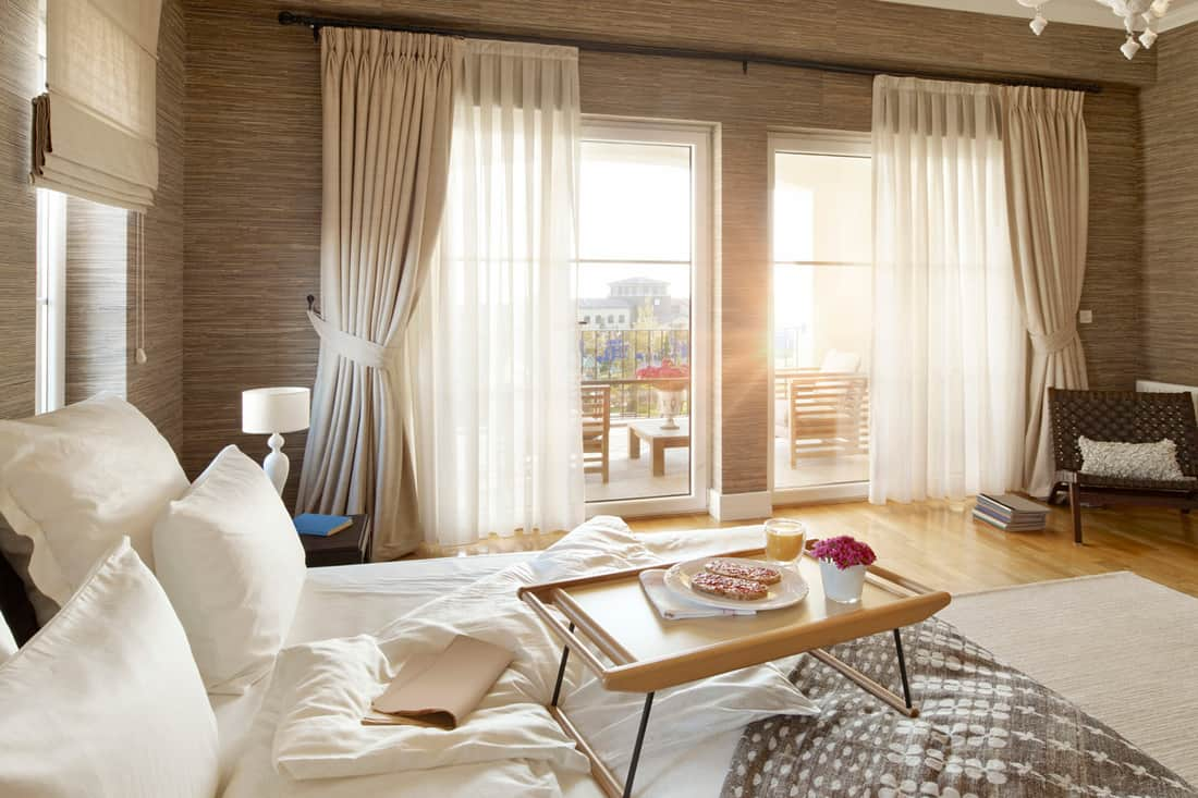 A beige colored bedroom with a white bedding set and beige curtains