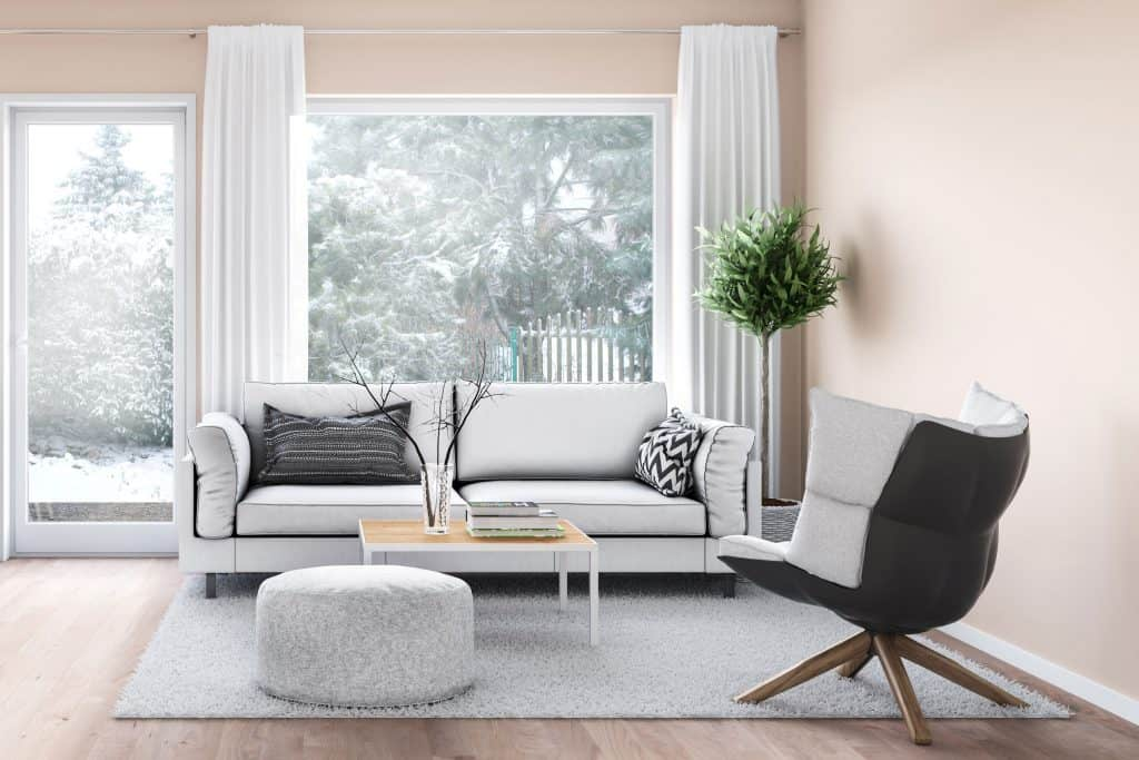 A beige colored living room with a gray couch and a black and white throw pillow