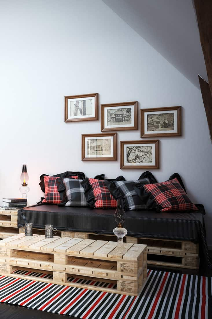 A black couch placed next to a white wall with picture frames on the wall
