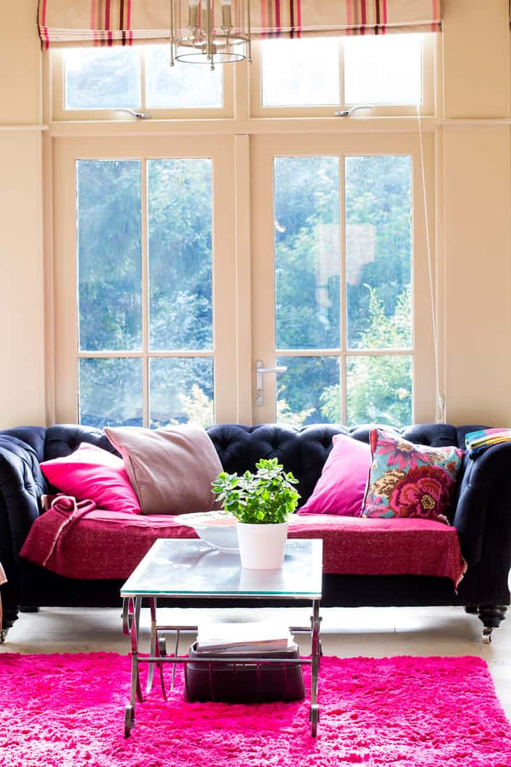 A black couch with pinks throw pillows and a pink rug on the floor