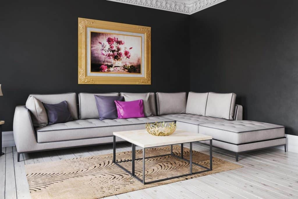 A black wall living room with a gray couch and a sectional couch and throw pillows on top