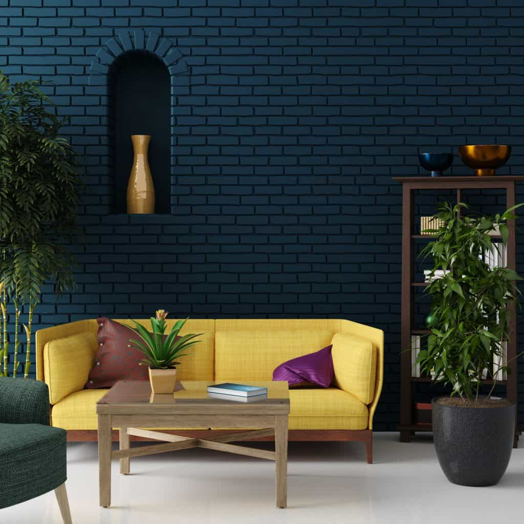 A blue brick patterned living room wall and a yellow couch with indoor plants
