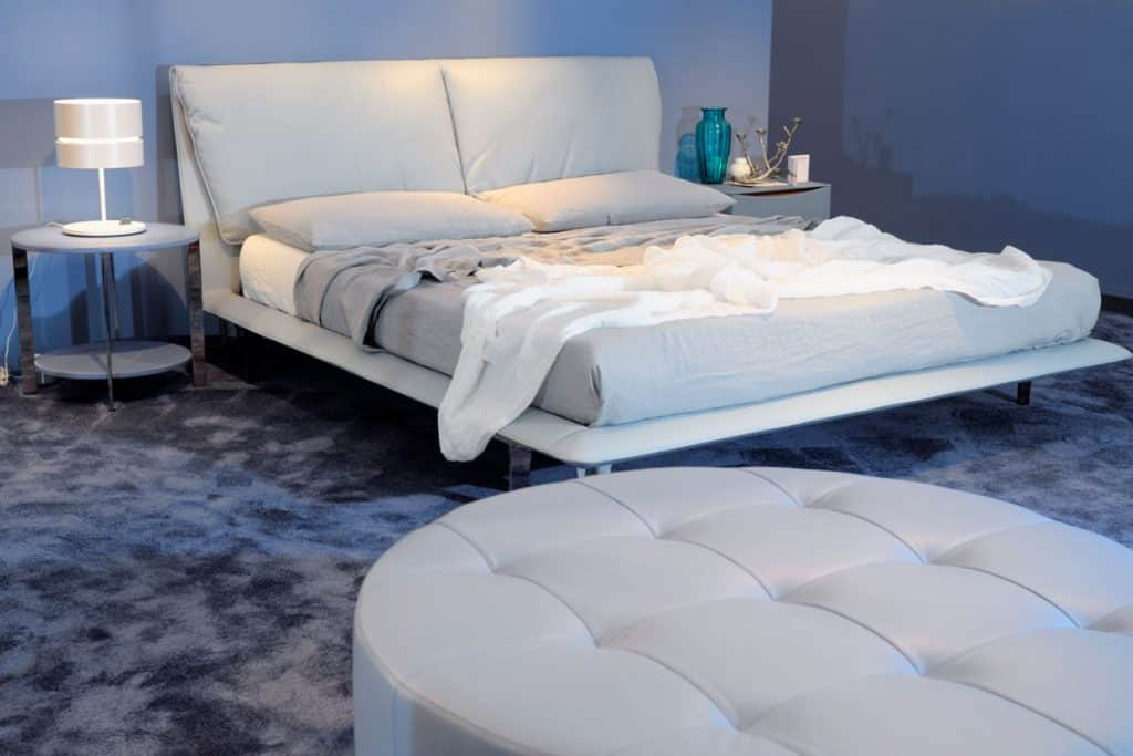 A blue colored bedroom with a white and gray bedding set