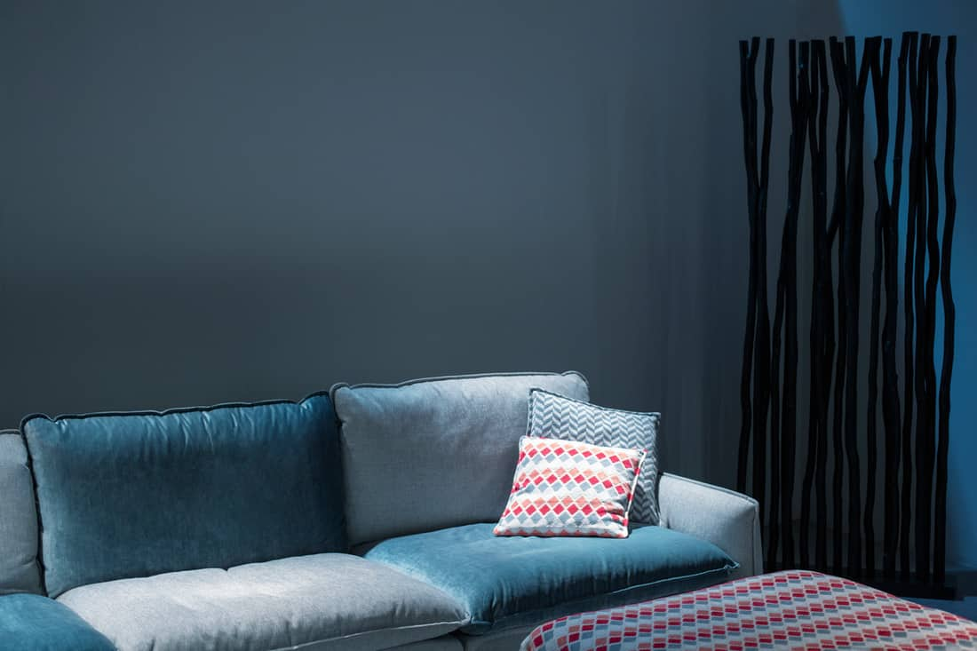 A blue colored couch with matching blue walls