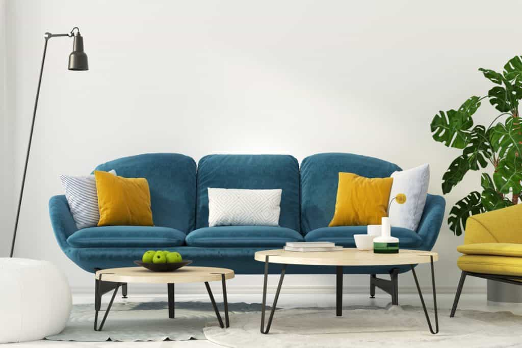 A blue colored couch with throw pillows and coffee tables on front