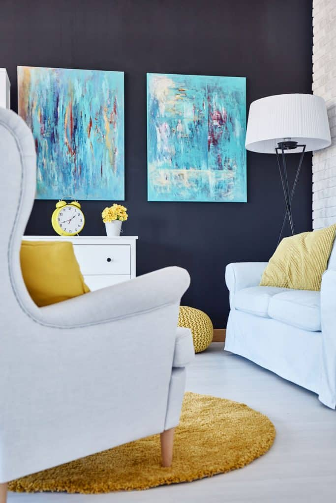 A blue colored living room with a white accent chair and a sleeper couch