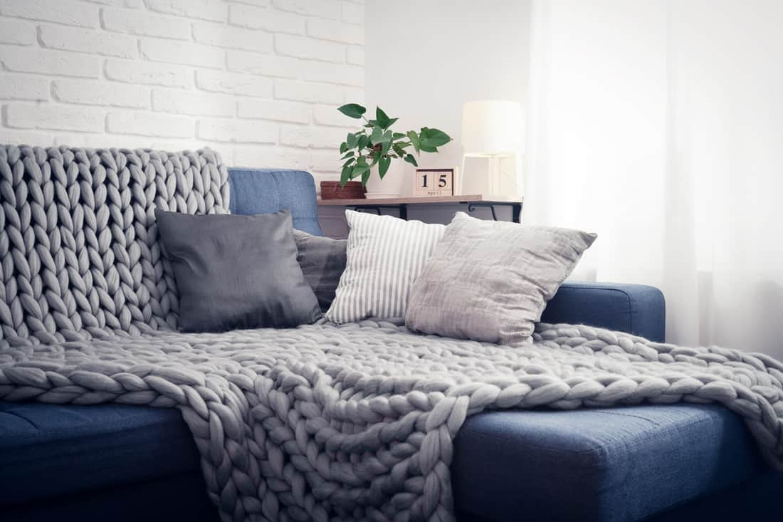 A blue colored sofa with a comfortable blanket and throw pillow placed on top