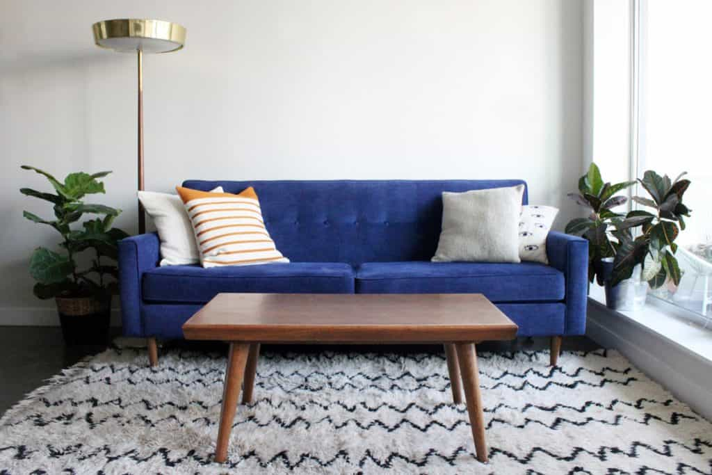 A blue colored sofa with white colored walls