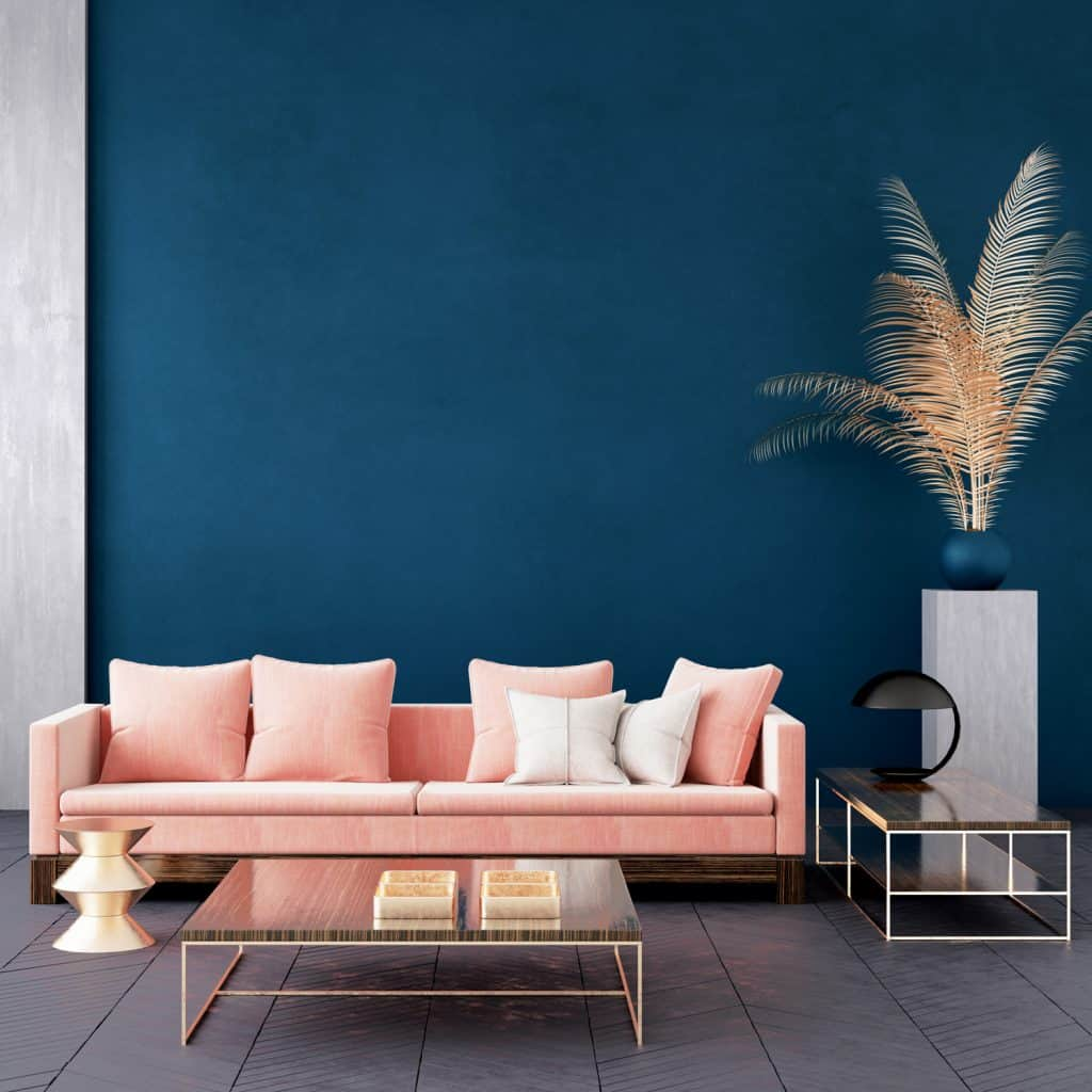 A blue colored wall with a a pink throw pillow, and a coffee table in front
